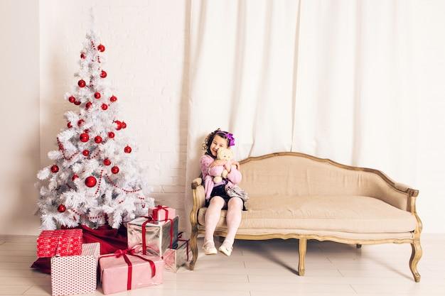 Menina de sorriso do miúdo que guarda o urso de peluche branco com árvore de natal dentro. infância.