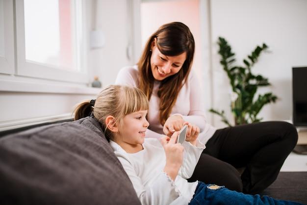 Menina de sorriso e sua mãe que usa o smartphone.