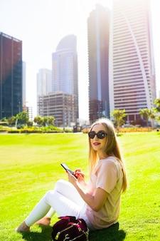 Menina de sorriso em óculos de sol pretos senta-se no gramado verde-claro em dubai