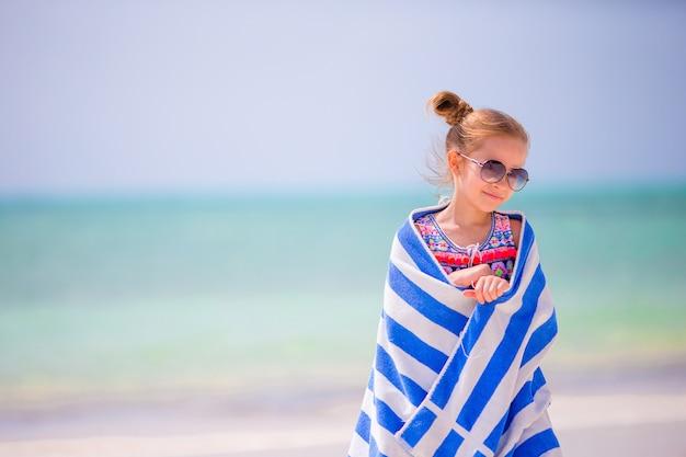 Menina de sorriso feliz adorável com a toalha em férias da praia