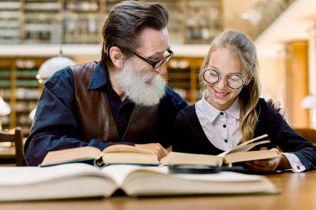 Menina de sorriso feliz com seus livros de leitura alegres do avô na biblioteca. menina sorridente com seu professor sênior estudando juntos na biblioteca