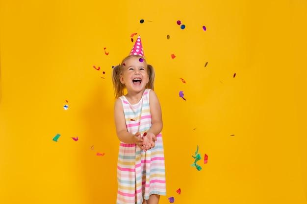 Menina de sorriso feliz da criança do aniversário no copo cor-de-rosa cercado voando pelos confetes na parede amarela colorida. celebração, infância, emoções.