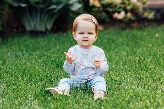 Menina de sorriso no prado que olha direito na câmera e na grama da terra arrendada nas mãos, bebê pequeno bonito.