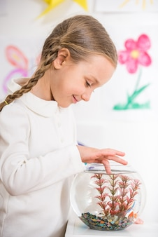 Menina de sorriso no pulôver branco que joga com peixes do ouro.