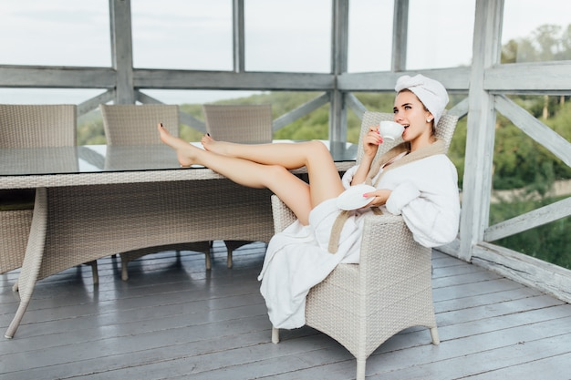 Menina de sorriso nova, bonita na veste branca, sentando-se no terraço do hotel e bebendo o café.