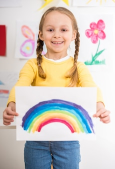 Menina de sorriso pequena no pulôver amarelo que guarda uma imagem.