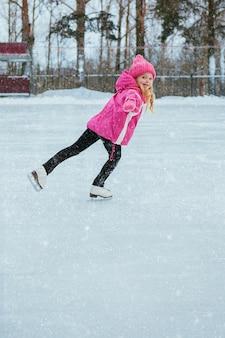Menina de sorriso pequena que patina no gelo no desgaste cor-de-rosa. inverno
