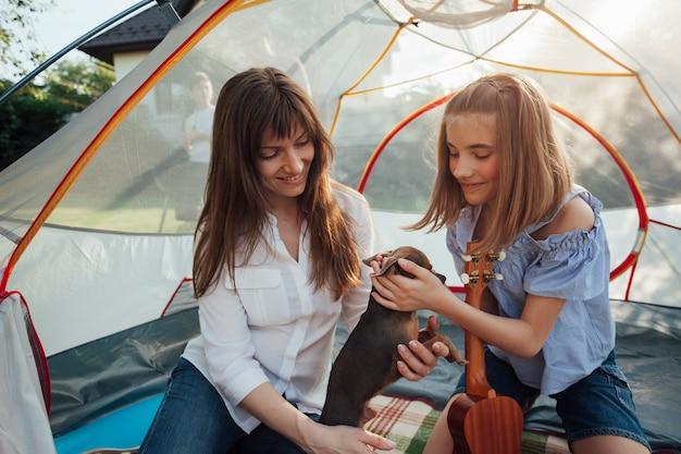 Menina de sorriso que afaga o cão pequeno que guarda por sua mãe que senta-se na barraca