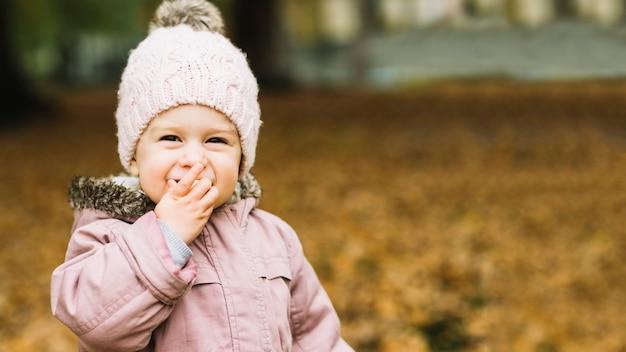 Menina de sorriso que come o petisco na floresta do outono