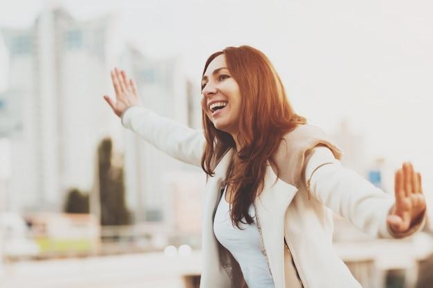 Menina de sorriso que corre com mãos no ar ao ar livre.