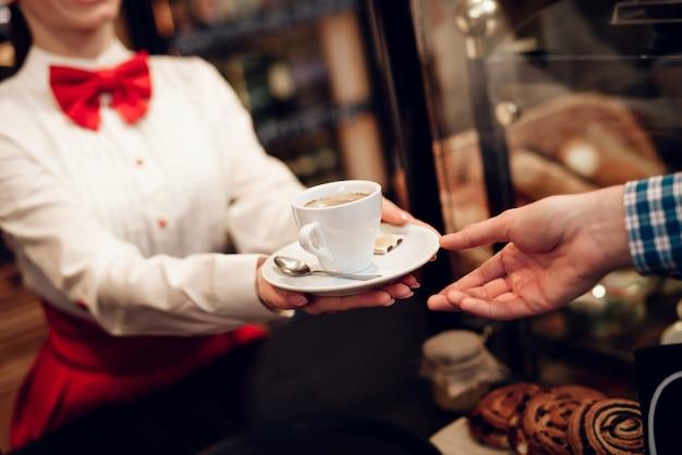 Menina de sorriso que dá a xícara de café ao homem novo.
