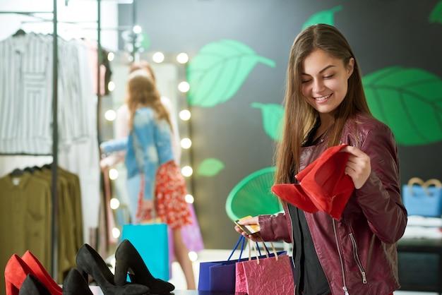 Menina de sorriso que escolhe sapatas vermelhas na loja.