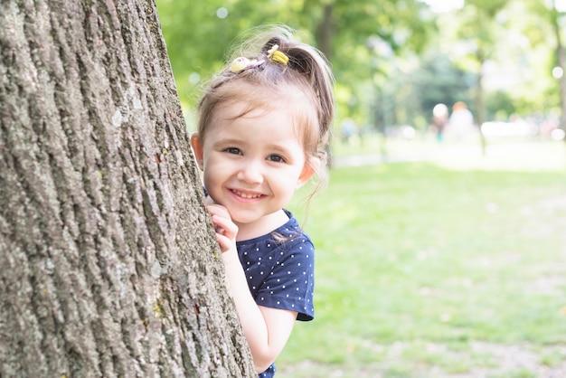 Menina de sorriso que está atrás do tronco de árvore que espreita no jardim