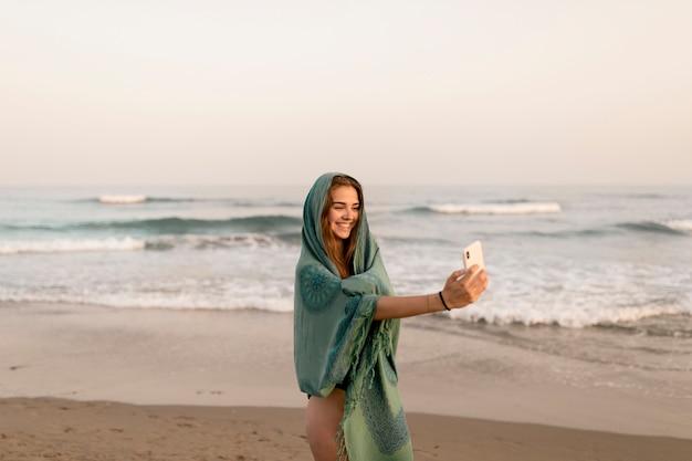 Menina de sorriso que está perto do litoral que toma o autorretrato do telefone móvel