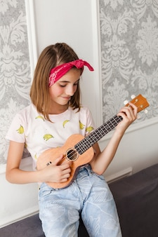 Menina de sorriso que joga o ukulele em casa