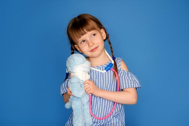 Menina de sorriso que joga um doutor e que escuta um urso de peluche com um estetoscópio isolado em uma parede azul. jogo de clínica veterinária. o conceito da futura profissão.