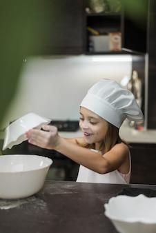 Menina de sorriso que mistura ingredientes na bacia no worktop da cozinha