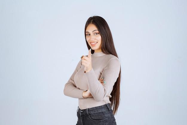 Menina de suéter cinza fazendo o polegar para cima o sinal.