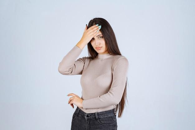 Menina de suéter cinza segurando seu rosto e cabeça.