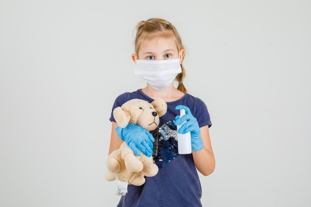 Menina de t-shirt, luvas e máscara médica segurando spray de mão e urso, vista frontal.