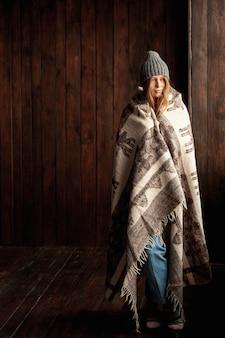 Menina de tiro completo com chapéu e cobertor dentro de casa