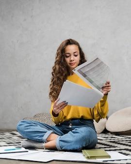 Menina de tiro completo olhando por cima de suas anotações