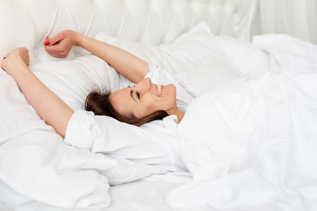 Menina de tiro médio, acordando na cama confortável
