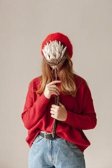 Menina de tiro médio, cobrindo o rosto com flor