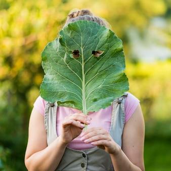 Menina de tiro médio, cobrindo o rosto com folha