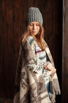 Menina de tiro médio com cobertor e chapéu dentro de casa