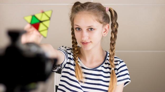 Menina de tiro médio com pirâmide de rubik