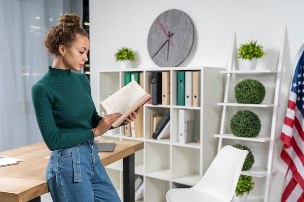 Menina de tiro médio com um livro dentro de casa