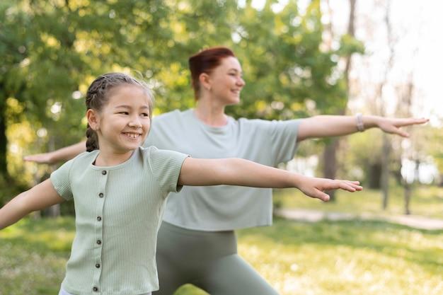 Menina de tiro médio e mulher se exercitando