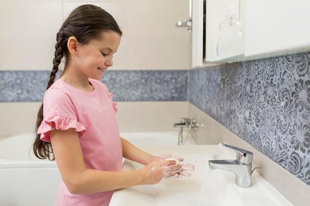 Menina de tiro médio, lavar as mãos