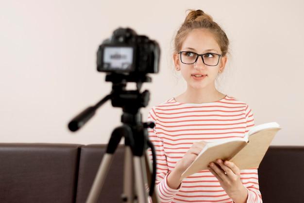 Menina de tiro médio lendo na câmera