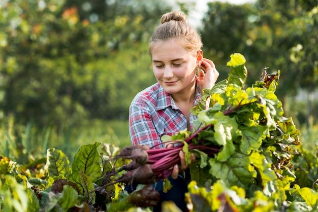 Menina de tiro médio pegando legumes