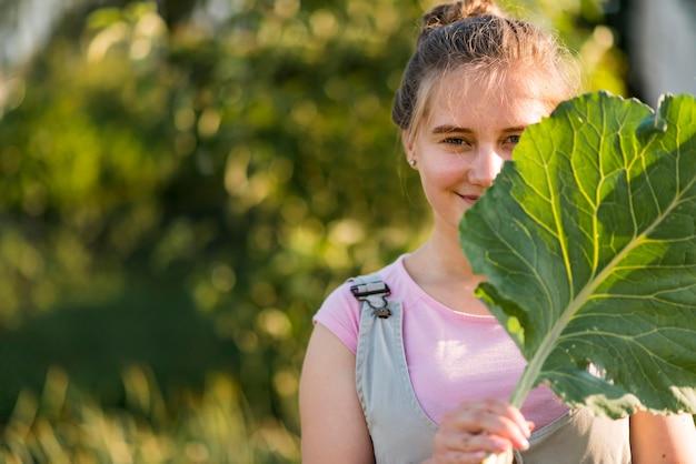 Menina de tiro médio, segurando a folha de alface