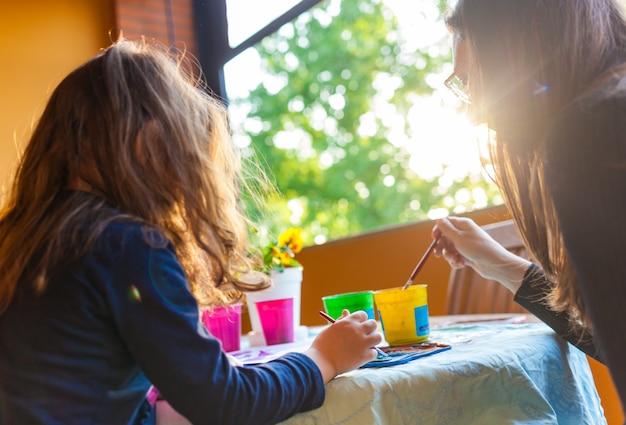 Menina de três anos colorir com a mãe com aquarelas.