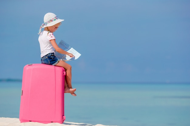 Menina de turistas pouco com mala grande na praia tropical branca