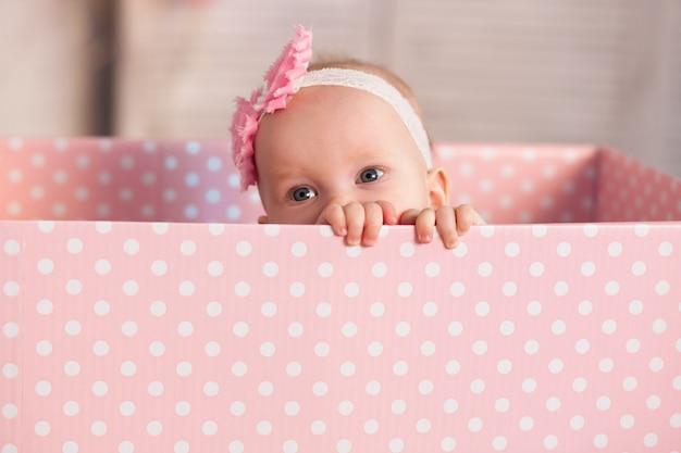 Menina de um ano de idade em uma roupa rosa suave parece fora de uma caixa festiva. aniversário feriado