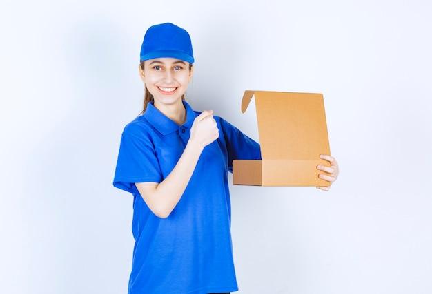 Menina de uniforme azul, segurando uma caixa de papelão para viagem aberta e mostrando o punho.