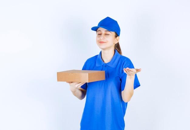 Menina de uniforme azul segurando uma caixa de papelão para viagem e cheirando a comida.