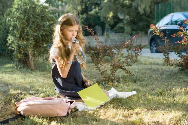 Menina de uniforme escolar com mochila sentado no gramado