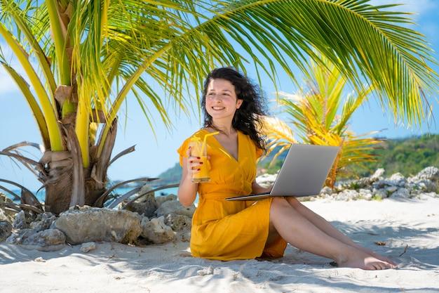 Menina de vestido amarelo em uma praia tropical trabalha em um laptop e bebe manga fresca. trabalho remoto, freelancer de sucesso. trabalha de férias.