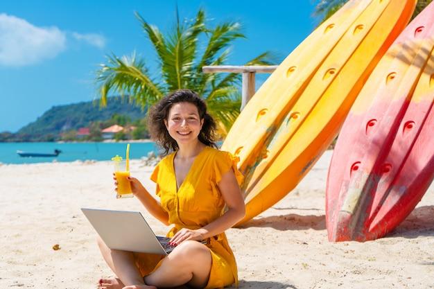 Menina de vestido amarelo em uma praia tropical trabalha em um laptop perto de caiaques e bebe manga fresca. trabalho remoto, freelancer de sucesso. trabalha de férias.