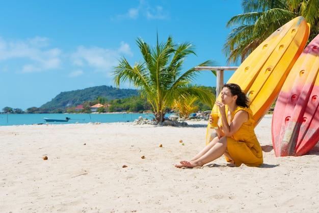 Menina de vestido amarelo na praia tropical trabalha no laptop perto de caiaques e bebe manga fresca. trabalho remoto, freelancer de sucesso. trabalha de férias.