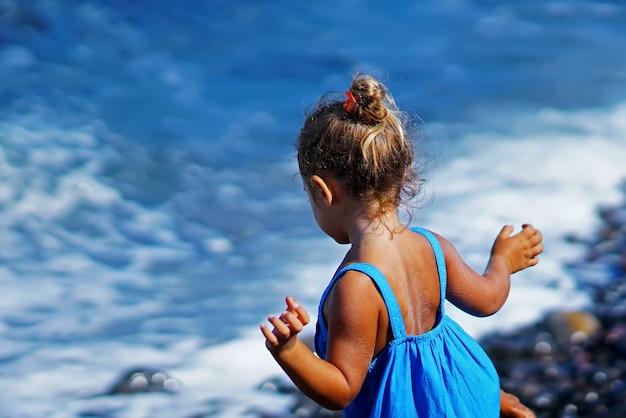 Menina de vestido azul, brincando na praia paradisos em santorini