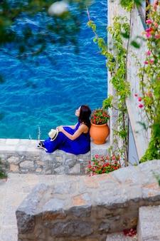 Menina de vestido azul na cidade da ilha de hydra