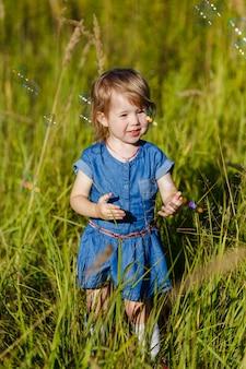 Menina de vestido azul, tentando pegar bolhas de sabão no parque de verão