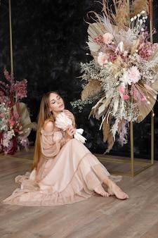 Menina de vestido boho no arco com flores artificiais